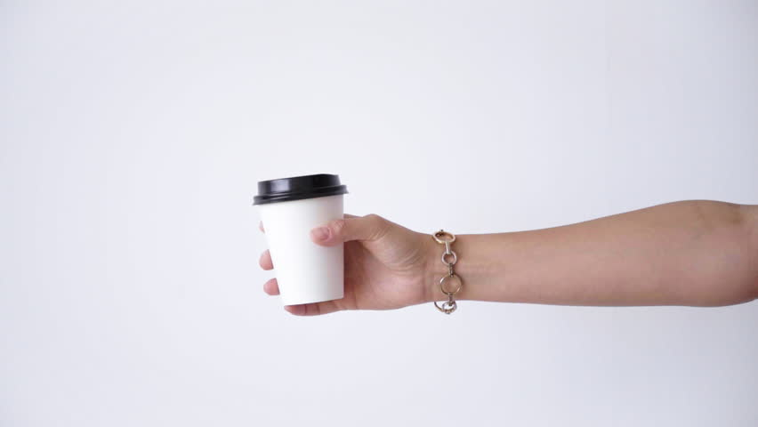 Woman hand with bracelet moves smoothly white paper cup from right side to center and takes away | Shutterstock HD Video #17539576
