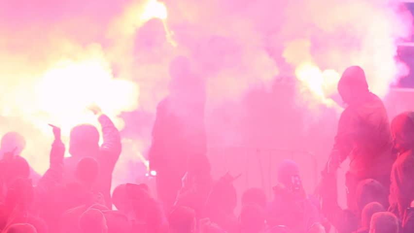 Hooligans using burning flares, smoke bombs at tribunes during football game. Aggressive teenage spectators supporting sport team, breaking rules. People demonstrating protest at stadium, vandalism