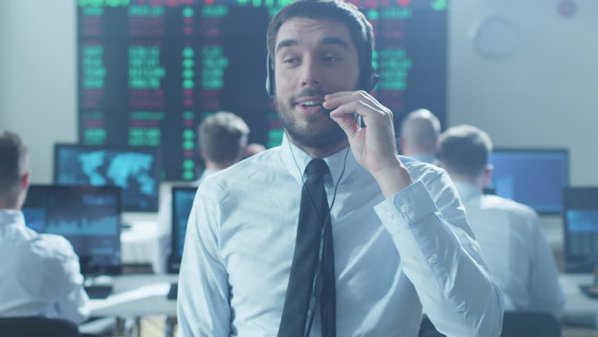 Caucasian Ethnicity Stockbroker is Actively Talking using Headset at Stock Exchange. Shot on RED Cinema Camera in 4K (UHD).