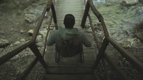 Young disabled man in wheelchair on a wooden bridge over river in the forest