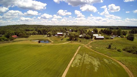 Working farm aerials, barn and buildings. Upstate New York. Puffy clouds. Float over differt views of a small farm.