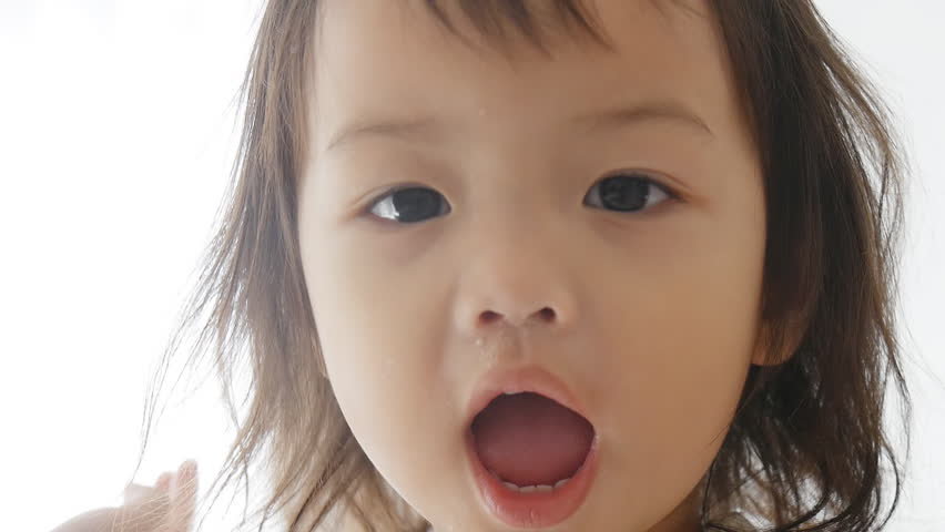 Asian child playing peek a boo at home