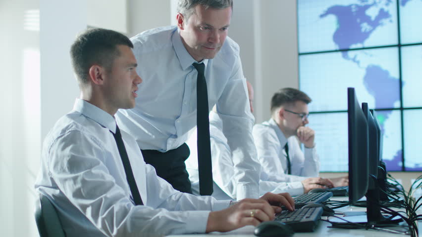 Team of Professionals Working at the Computers in Bright Office. Experienced Worker helps Trainee. Shot on RED Cinema Camera in 4K (UHD). | Shutterstock HD Video #17607358