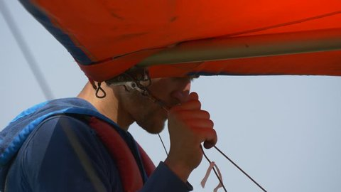 Man holds the nose of the hang glider