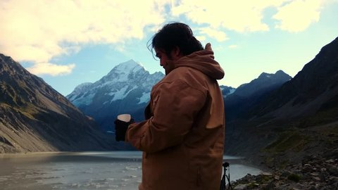 Man Drinking From Thermos While Enjoying The Scenery at Hooker Lake Glacier Terminal, Mount Cook National Park, New Zealand. Camera Slide Left