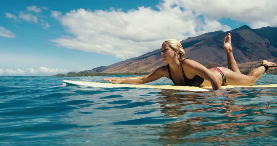 Beautiful girl paddling surfboard over blue ocean wave