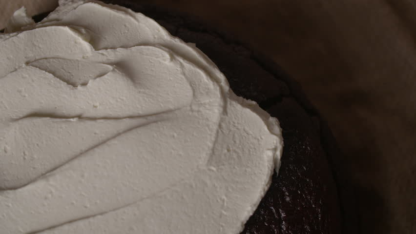 Overhead close up white cream cheese topping spread on Guinness chocolate cake