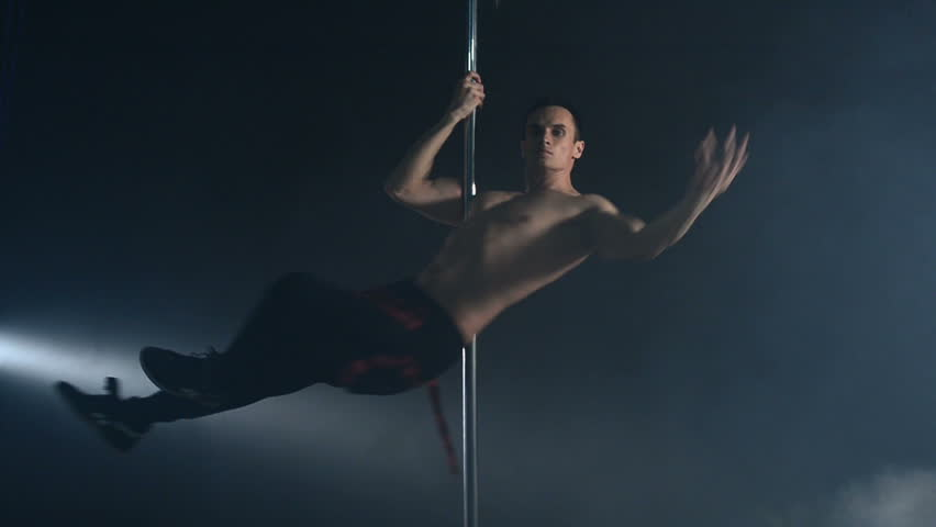 Young strong sexy pole dance man dancing on a black background