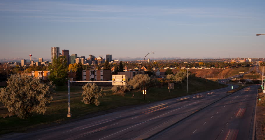 Calgary, Alberta, Canada - Crossing of Trans-Canada Highway 1 and Alberta Provincial Highway 2 with view to downtown and Canadian Rockies after sunrise - Timelapse with pan left / right - October 2014