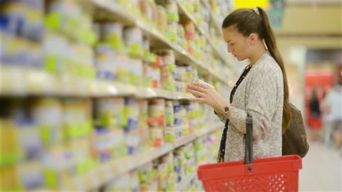 Young woman chooses baby food in the supermarket, Mother chooses food for their child in the market, girl stands near the supermarket shelf and selects the products
