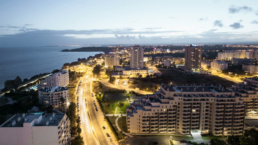 4 K time laps video of the City on the bank of ocean and light trails at night. Portimao, Praia da Rocha, Praia de Vau, Lagos. Algarve,  Portugal. 4096 x 2304