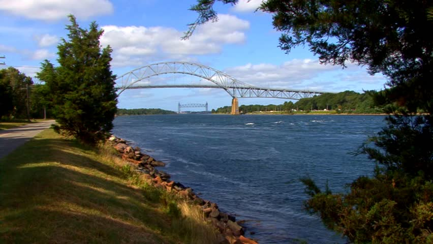 Beautiful sunny day at Cape Cod canal showing the Bourne & distant train bridge, wind turbine, bike/walking path as motor boat passes by
