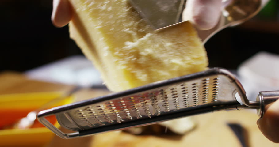 Expert chef grating parmesan over spaghetti al pomodoro, a typical dish of Italian pasta cooked according to tradition