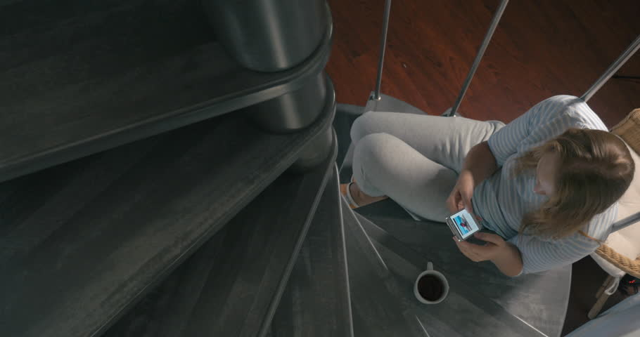 Cinemagraph - high-angle shot of young woman sitting on the winding stairs and watching newsfeed in her smartphone | Shutterstock HD Video #17733649