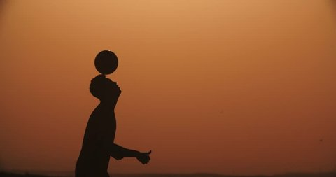 football player silhouette , practicing with the ball,the sunset Golden hour,heading slow motion