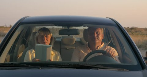 Steadicam shot of senior couple having a slow car ride in rough country at sunset. Man driving and woman using tablet computer
