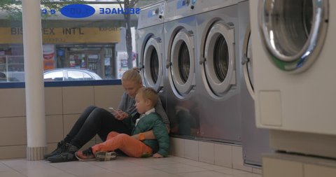 Mother and son waiting in the laundry. They sitting on the floor near the washing machines and using smart phone
