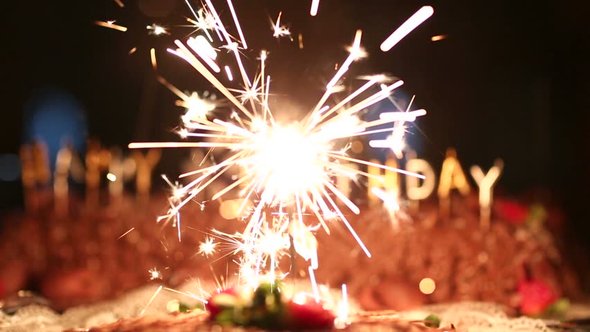 Burning Sparkler On A Birthday Cake And With Happy Written In The Background Like Firework