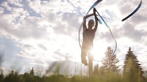 Dance young gymnast with ribbon on sunset sky background. Rhythmic gymnastics.
