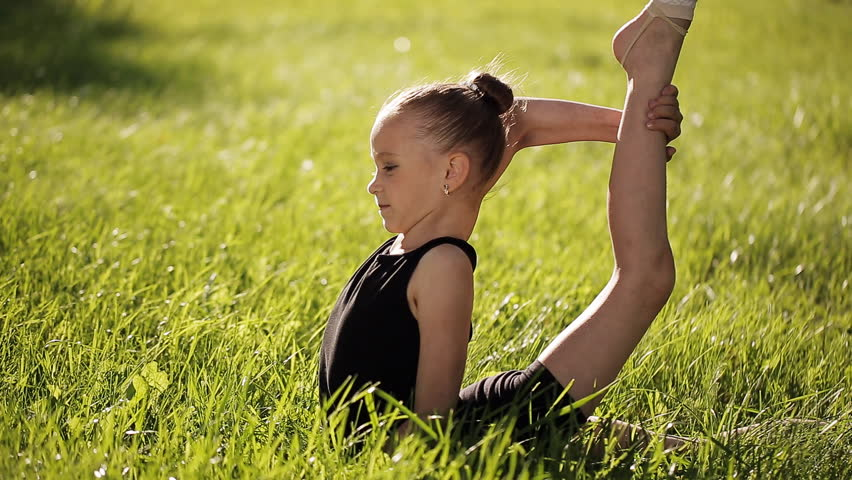 Petite flexible girl does in the grass complex gymnastic exercises. | Shutterstock HD Video #17772094