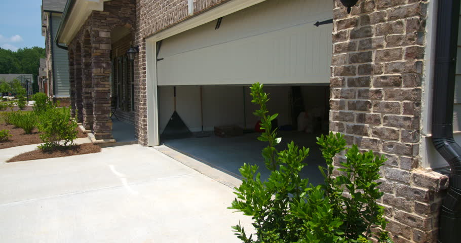 Home Garage Door Opens Angled Lowering. lowering shot on an angled front exterior of a new residential home as the garage door opens