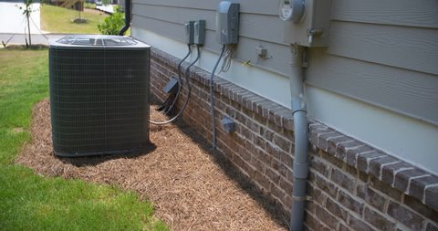 Air Conditioning Unit and Electric Meter Rise Side of Home. slow rise on the side of a home showing the electric meter in the foreground and an central air conditioning unit in the background