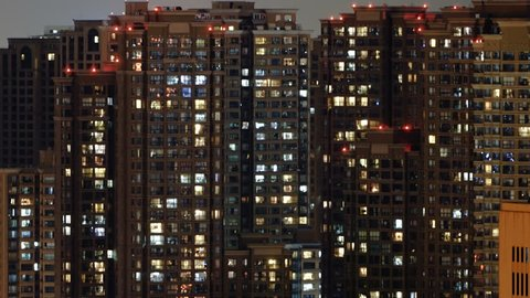 Time lapse of apartment building at night. Timelapse of residential flats windows lighting up and turning off overnight in Shanghai, China. Countless people live in massive building.