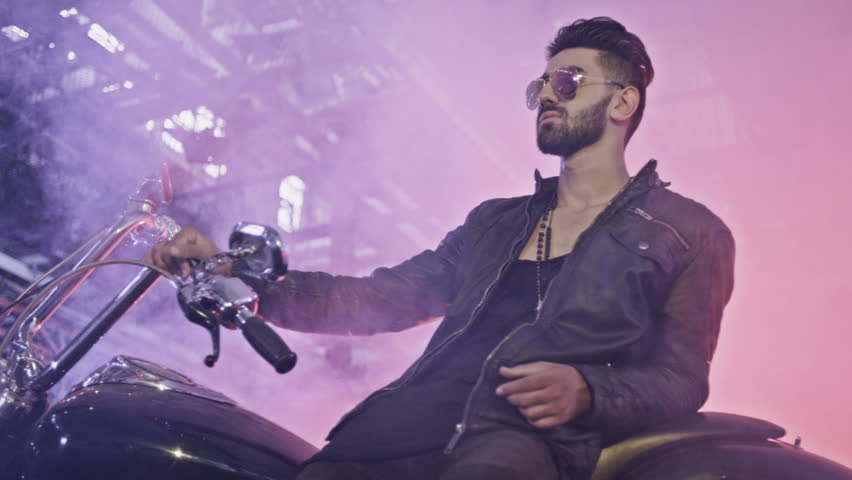 Portrait of stylish biker with his motorcycle.. Shot on RED EPIC Cinema Camera in slow motion.