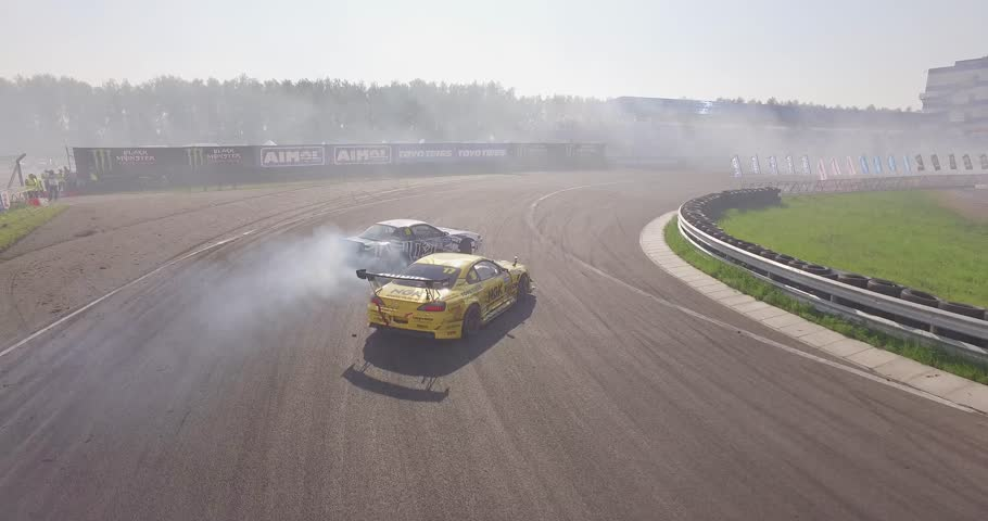 NIZHNIY NOVGOROD, RUSSIA - MAY 23, 2014 : Aerial shot of cars drifting with lots of smoke during drift competition named Russian Drift Series in Nizhniy Novgorod, Russia.