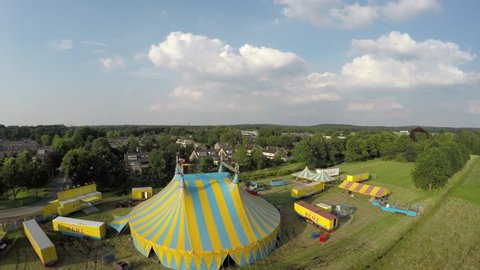 Aerial moving backwards from circus tent colored in blue and yellow stripes also showing circus trucks and smaller tents and buildings on top of structure some flags are placed moved by wind 4k