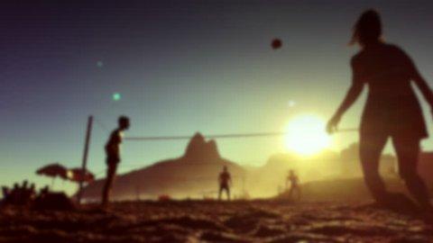Defocus silhouettes playing Brazilian beach futevolei (footvolley), a sport combining football (soccer) and volleyball, at sunset on Ipanema Beach, Rio de Janeiro, Brazil