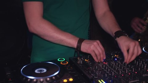 Dj spinning at turntable, look in camera. Man play saxophone. Party in nightclub. Music
