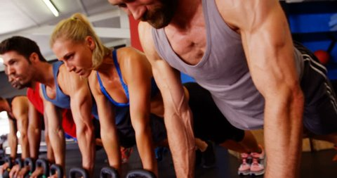 Group of people performing push-up exercise with kettlebell in gym 4k