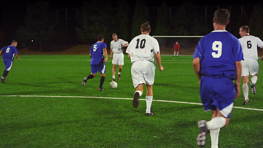 Soccer players pass the ball down the field at night and make a goal and celebrate, in real time