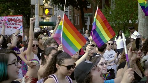 NEW YORK - JUNE 25, 2016: women waving rainbow flags in NYC. The Annual Dyke March is an unofficial event celebrated the day before the Gay Pride Parade.