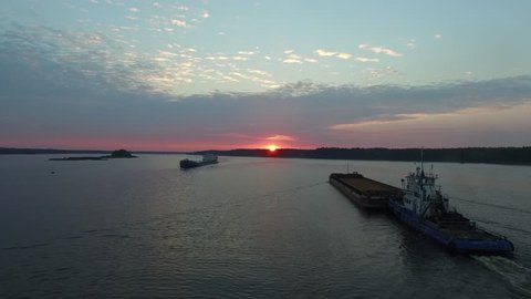Two ?argo transport ship sailing on a wide river. Sunrise. The island in the middle of the river. Flying near the barges on the river floating towards each other. Aerial view.
