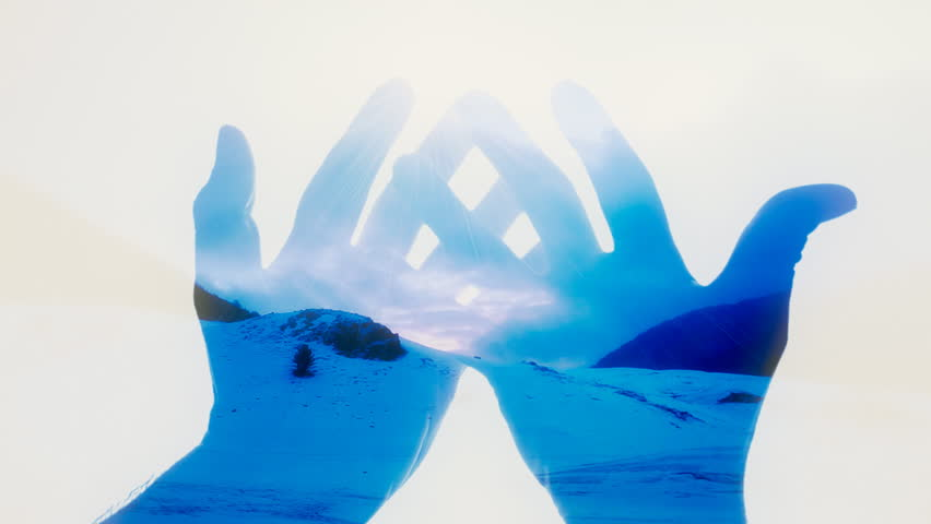 A pair of crossed hands forming a cup appear and reveal a scene in double exposure: morning or dusk on a mountain full of snow.