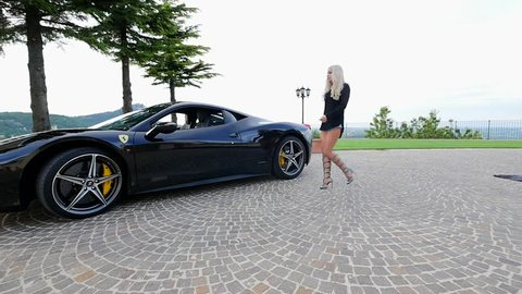 SAN MARINO, ITALY - JUNE 21, 2016: Beautiful young woman with Ferrari 458. Ferrari S.p.A. is an Italian sports car manufacturer, founded by Enzo Ferrari in 1939. Illustrative editorial.