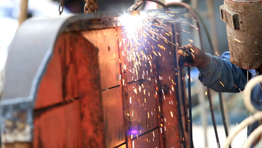 A man welding steel on the part of fishing boat at the harbor