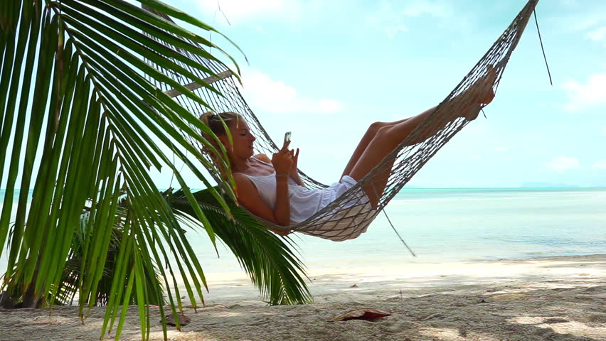 Young woman lying in a hammock on the beach with phone in hand - HD stock - Woman Using Mobile Phone In A Hammock On The Beach Stock Footage