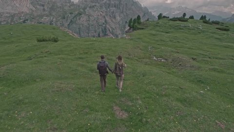 Drone flying over a couple who walks on the field in Tre Cime di Lavaredo, Italia.