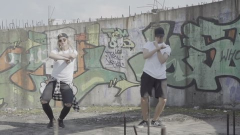 Video of active young couple dancing hip hop choreography in an abandoned building with graffitis on the wall in slow motion..