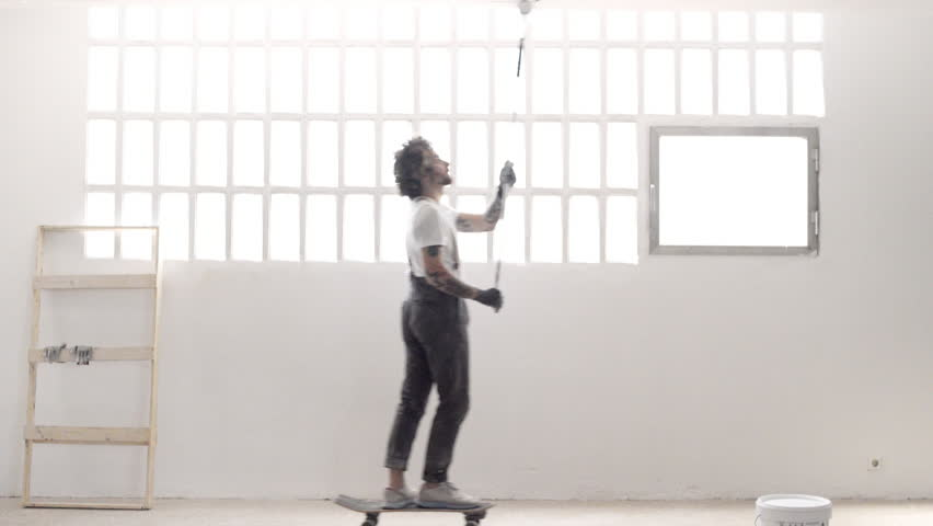 Funny curly man wears pants with suspenders skates with paint bucket from one side to other and falls in the end, small comedy about home renovation