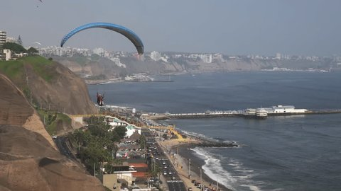 paraglider with a blue canopy flies at miraflores in lima, peru