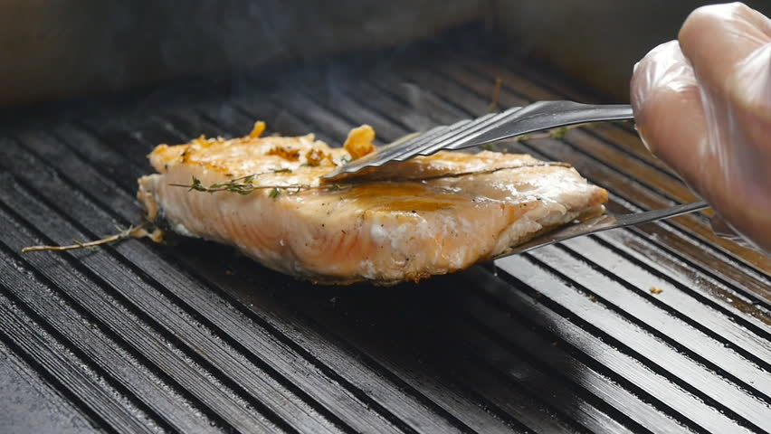 Grilled red fish steak salmon on the grill in slow motion