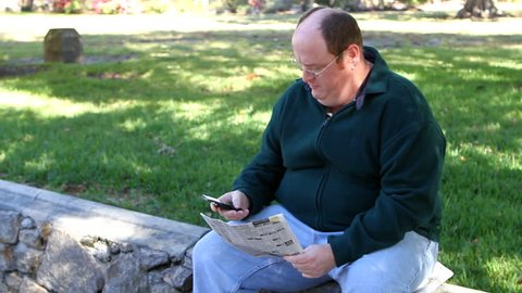 Unemployed obese man uses a cell phone to call about a job in the want ads section of the newspaper while in the park.