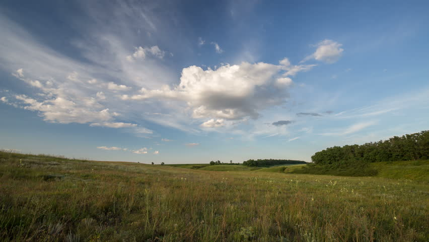 Russia, timelapse. The formation and movement of clouds over summer endless green fields of grass in the steppes of the Don.