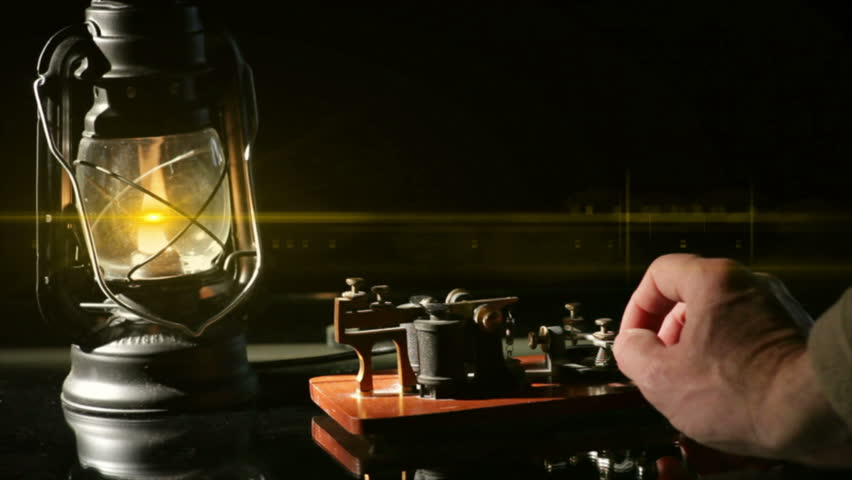 The flame from an oil latern throws a lens flare across a telegrapher sending a telegraph message.