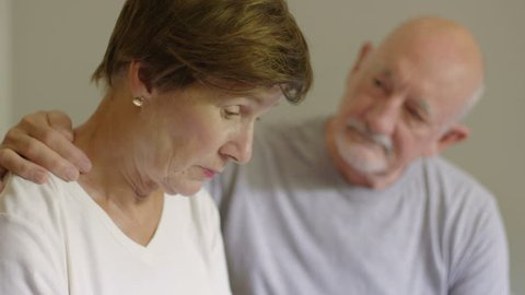 Older man comforting older woman