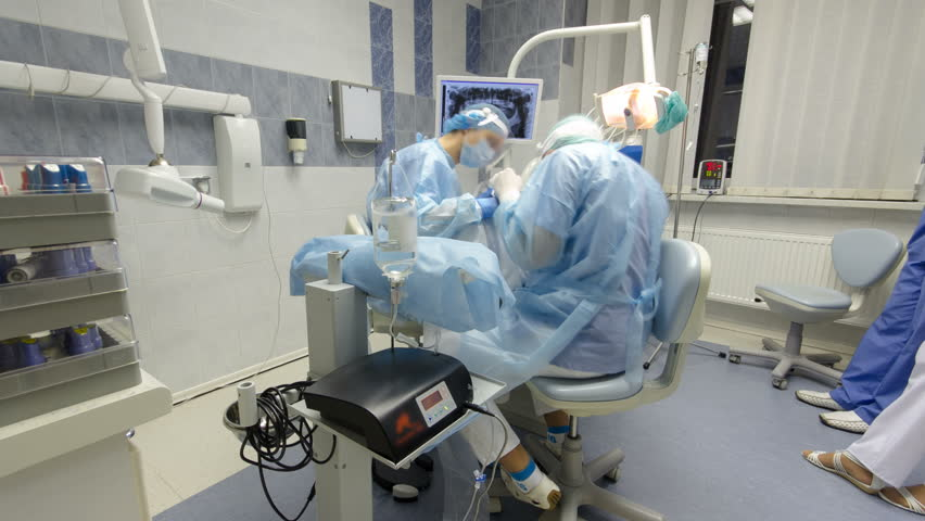 MOSCOW - CIRCA OCTOBER 2015: Dentists during surgery for implant placement timelapse. Dentist team working with patient